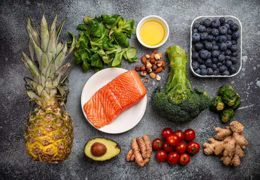 Anti inflammatory diet concept. Set of foods that help to reduce inflammation - plant based ingredients, fresh fruit, green vegetables. Healthy diet products, top view, stone background