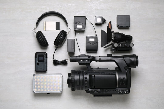 Flat lay composition with camera and video production equipment on light grey background
