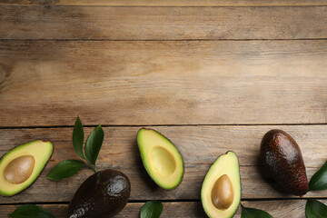 Whole and cut avocados with green leaves on wooden table, flat lay. Space for text Wall mural
