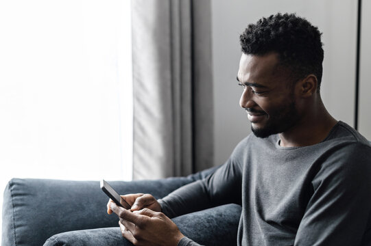 Side view of a young African-American guy is using smartphone sitting on the comfortable sofa at home. A smart multi-ethnic millennial is scrolling news feed, chatting online or answering messages
