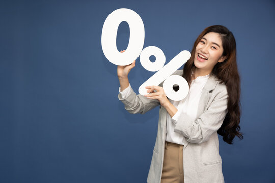 Portrait of Asian business woman showing and holding 0% number or zero percent isolated over deep blue background
