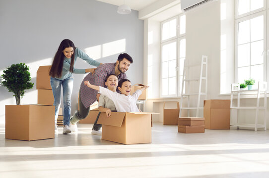 Joyful family with kids having fun in new home. Happy excited first-time buyers with children playing with boxes in the living room. Real estate, residential mortgage, moving into dream house concept