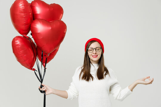 Young woman in sweater red hat glasses hold hands in yoga gesture, relaxing meditating celebrating birthday holiday party hold bunch heart air inflated helium balloons isolated on white background.