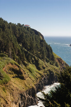 A lush green hill sits up over the ocean with cliffs plunging down towards the water below.