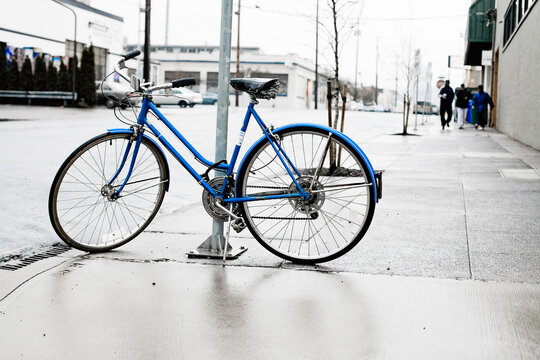 A blue bike is chained up to a street sign on this rainy day in the pacific northwest.