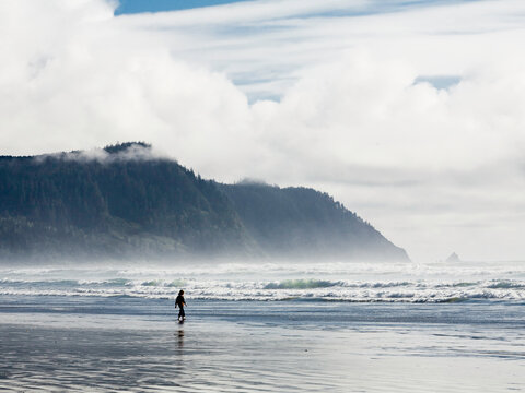 A cloudy day at the beach in Gearhart, Oregon. A lone figure walks out into the shallow waters as the tides recede.