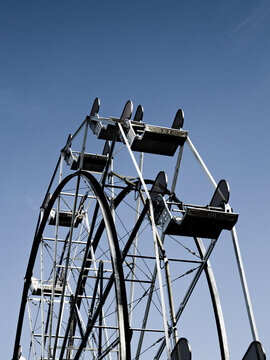 The top of an empty ferris wheel stands cold against a dark blue sky.