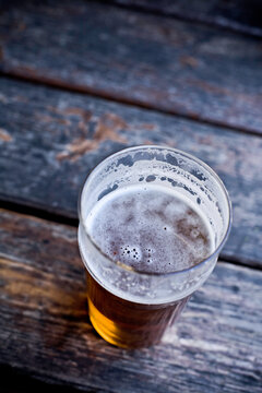 Top down view of a pint of beer sitting on wooden, picnic table that has been sipped on