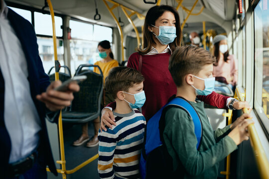Mother and kids wearing protective face masks while commuting by public transport.