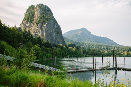 A dock stretches out into the water with a view of mountains and foliage in the background.