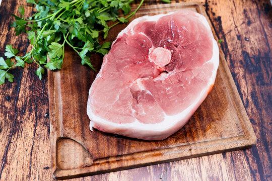 slice of fresh pork on a wooden cutting board