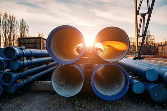 Stack of cast iron pipes in loading area waiting for transportation