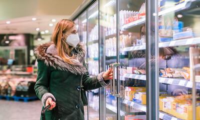 Woman at supermarket freezer section wearing face mask