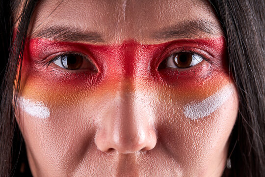 close-up eyes of indian woman confidently looking at camera, serious ethnic female with paintings on face. indian ehnicity, shaman concept