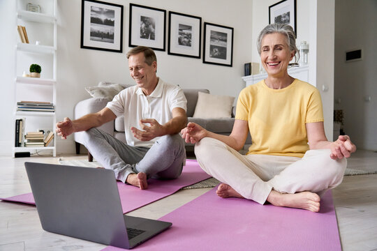 Happy relaxed old 60s couple having fun meditating together at home with laptop. Fit healthy senior mid aged man and woman laughing doing yoga exercise watching online class, feeling no stress free.