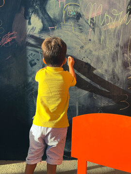 Colorful indoors picture of a boy alone playing and drawing on a chalkboard on the room's wall. Boy writing on the blackboard with a piece of chalk.