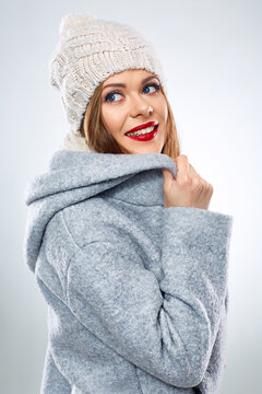 portrait of smiling woman in warm winter clothes looking up.