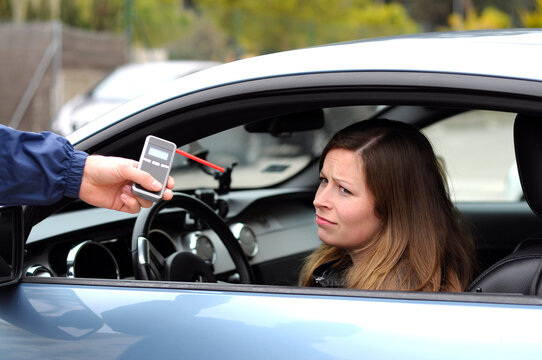 drink and drive crashed young female driver being subject to test for alcohol content with use of breathalyzer. she is devastated