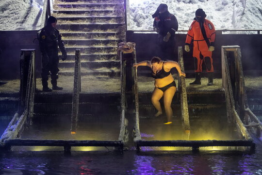 A woman steps down to take a dip in the icy waters of the Istra river during Orthodox Epiphany celebrations in the town of Istra