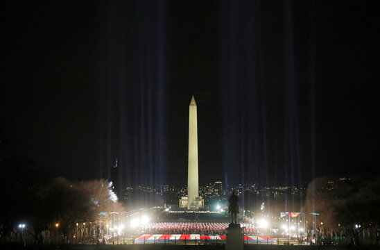"Spotlights illuminate the sky from the ""field of flags"" on the US national mall in honor of the upcoming inauguration of U.S. President-elect Joe Biden in Washington"