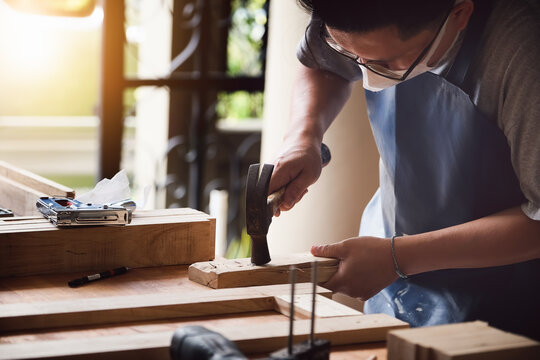 Entrepreneur  Woodwork holding hammer to assemble the wood pieces as the customer ordered