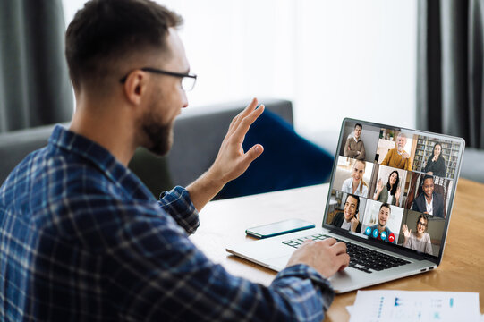 Video call, online business meeting, briefing. Successful caucasian freelancer waving hand and greeting colleagues during video conference. Distant work, online learning