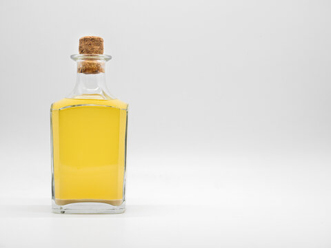 Glass bottle with alcohol drink closed with cork cap isolated on a white background. Transparent square bottle with yellow liquid. Front view of the vertical staying jar.