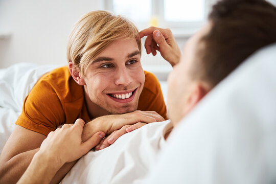 Happy homosexual couple lying in bed at home