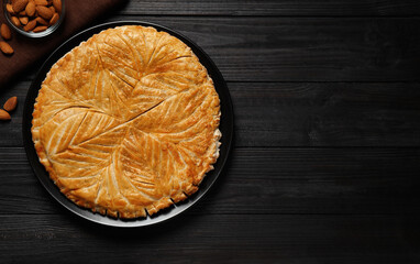 Traditional galette des rois and almonds on black wooden table, flat lay. Space for text
