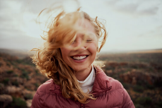 Portrait of young smiling woman face partially covered with flying hair in windy day standing at mountain - carefree woman