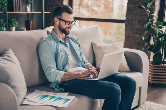 Photo portrait of man working on laptop sitting on couch in modern industrial office indoors