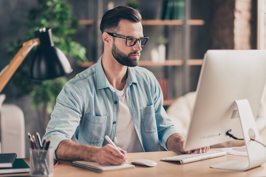 Photo portrait of smart guy taking notes working on computer at desk in modern industrial office indoors