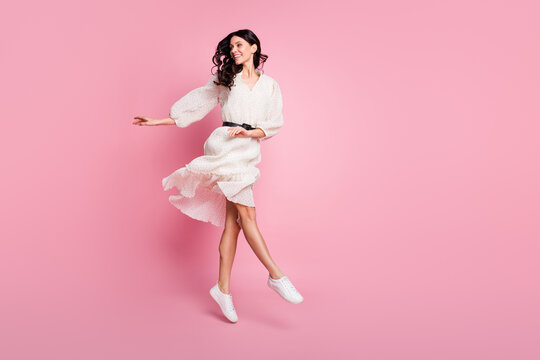 Full length body size photo of dancing woman in long dotted dress jumping looking blank space isolated pastel pink color background