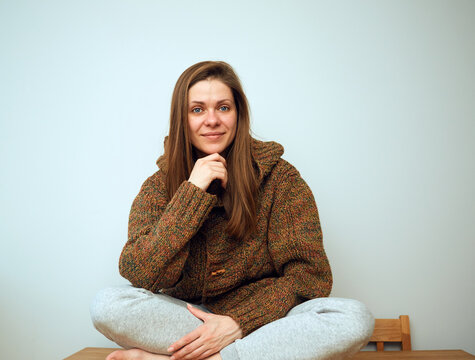 Woman wearing oversized knitted hoodie sits on a floor.