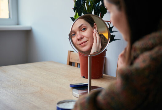 woman sitting at table and uses a moisturizer for her face and looks on mirror.