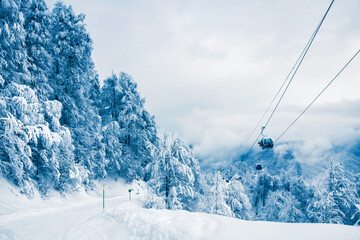 Ski slope and gondola lift in winter ski resort. Rosa Khutor, Sochi, Russia. Beautiful snow-covered mountains and forest, winter landscape