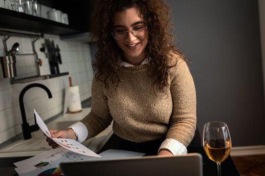 Portrait of young woman working at home in kitchen using laptop.