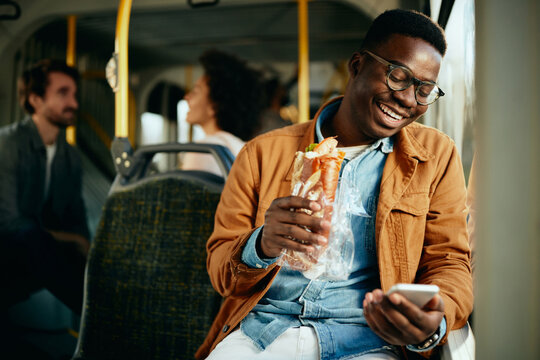 Happy black man eating a sandwich and using smart phone while commuting by bus.