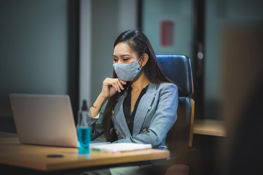 young business person wearing surgical face mask for protection with coronavirus covid-19, working in office with new normal protection lifestyle, social distancing and self-isolated