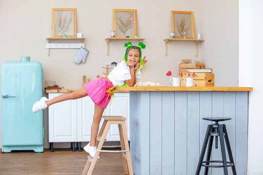 Little beautiful child girl in the kitchen at home happy and funny