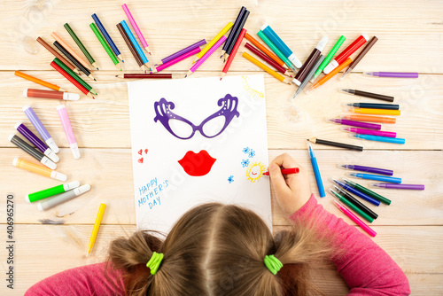 Little girl makes a greeting card to mom with an application for mother's day. Drawing and applique work is done by the child using colored pencils or felt-tip pens. View from above