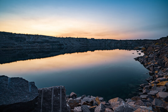 Old flooded stone quarry surrounded by stone waste from a mine work against a beautiful night sky