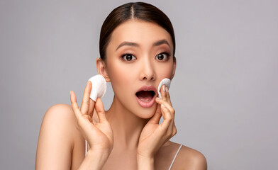 Beautiful young asian woman with Clean Fresh Skin on face . Chinese girl with clean  cotton pads. Facial  treatment . Cosmetology , beauty  and spa . Expressive facial expressions.  - fototapety na wymiar