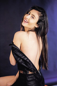 Sexy woman wearing little black dress . Portrait shoot in the studio . Black background