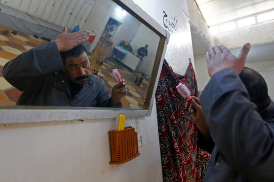 """A man looks at his reflection in a mirror as he combs his hair during a visit to a """"Hammam"""", a traditional steam bath, amid the spread of the coronavirus disease (COVID-19) in Najaf"""