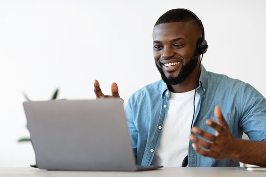 Video Conference. Cheerful african american man in headset making web call on laptop
