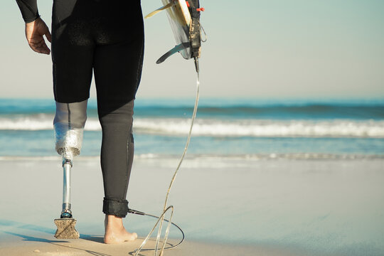 Unrecognizable disabled surfer going to water and carrying longboard. Cropped strong man wearing sportive swimsuit and holding surfboard. Physical disability, surfing and extreme sport concept