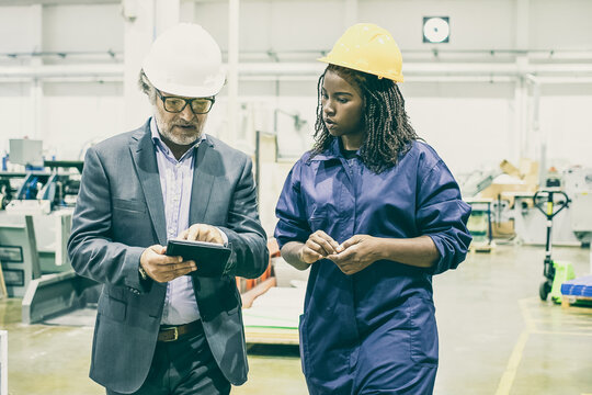 African American female worker listening work explanation from bearded boss. Professional confident manager pointing into tablet screen, walking and talking. Manufacture and digital technology concept