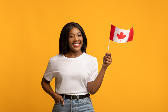 Happy black woman showing canadian flag on yellow