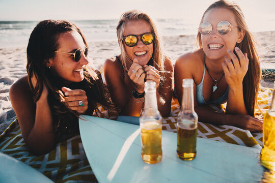 Happy group of female friends drinking beer at the beach and having fun on vacation